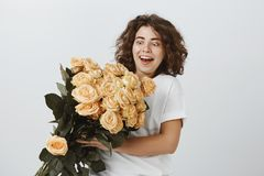 Someone has secret admirer. Pleasantly shocked attractive curly-haired woman holding large beautiful bucket of roses. Being surprised with gift, happy to stock image