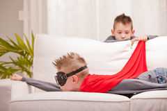 Someone have fun and some others not. Kids playing superheros on a sofa but one of them is not enjoying the game very much royalty free stock image
