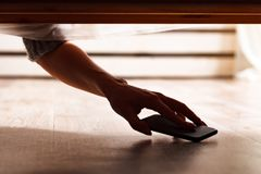 Someone is hiding a smartphone. Under the bed royalty free stock photos