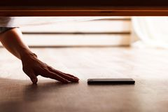Someone is hiding a smartphone. Under the bed royalty free stock images