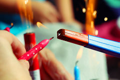 Someone holding pink birthday candle in the hand and light it a. With gasoline lighter. In the background there are lighted candles and fireworks stock photos