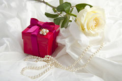 For someone I love. Gift box with ring pearls and rose on a satin background Royalty Free Stock Photos