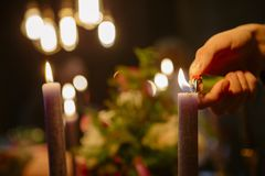 Someone lighting up candles on a festive wedding dinner table. D. Ark dim candle light. Copy space stock photos