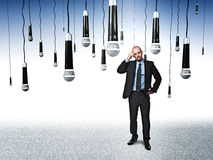 Someone listen me. Standing businessman and lots of microphone royalty free stock photo