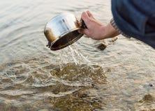 Someone myje garnek w rzece Zdjęcie Royalty Free