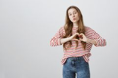 Someone needs love. Dreamy young woman in striped clothes showing heart gesture over chest, folding lips in kiss. Wanting mwah and confessing in tender Royalty Free Stock Photo