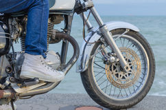 Someone on old motorcycle. Parking at the seaside in evening stock photo