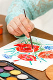 Someone painting poppy flowers. On a white sheet of paper royalty free stock image