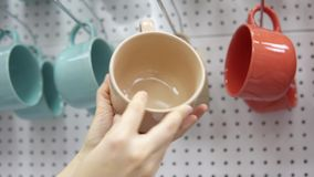 Someone picks a big ceramic cup in the supermarket. A young woman chooses a large ceramic cup in a supermarket in the dishes section. A female hand takes a