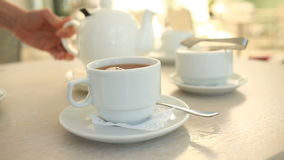 Someone pours tea from a porcelain white teapot into a white mug stock footage