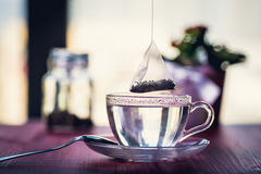 Someone preparing tea. Putting tea bag into glass cup full of hot water Stock Photography