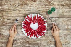Someone is preparing to eat heart made of chilly. On the white plate Royalty Free Stock Photo