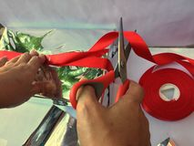 Someone is preparing to wrap a gift box. A group of wrapped gift boxes for someone special in greeting moments. They're decorating with red satin ribbon. For stock photography