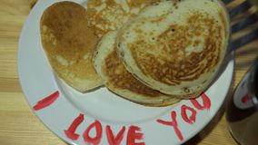 A plate with pancakes in the form of a heart and a mug with coffee on a table. Someone puts a mug of coffee on a wooden table, then on a white plate with a red stock footage