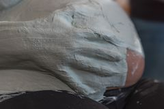 Someone puts plaster on the belly of a expectant young mothe royalty free stock image