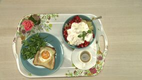 Someone putting a cup of coffee and vase on a tray. With fried egg, green parsley and berry salad top view stock video footage