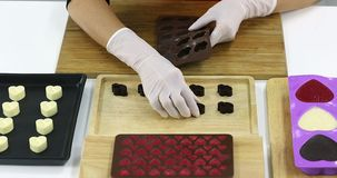 Someone removed the chocolate from mold. Close up scene video of someone removed the chocolate from the heart shaped mold, arrange the chocolate on a wooden stock video