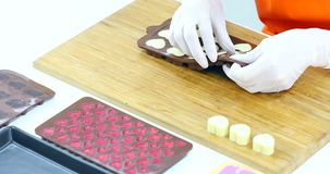Someone removed the chocolate from mold. Close up scene video of someone removed white chocolate from the heart shaped mold, arrange the chocolate on a wooden stock video footage