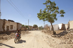 Someone riding a motorbike, Ethiopia. Someone riding a motorbike along a dirt road with crumbling buildings and rubble either side of the road. Ethiopia royalty free stock photos