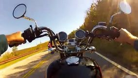 Someone riding a motorcycle on a curvy and forested mountain road. Video of someone riding a motorcycle on a curvy and forested mountain road stock video footage
