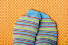 Someone rubbing his or her feet wearing colorful socks Stock Photos