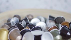 Someone`s hand abruptly takes coffee capsule out of bowl with other capsules. Someone`s hand is abruptly taking out small, orange, round-shaped coffee capsule stock video footage
