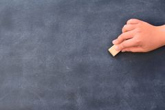 Someone's hand cleaning the chalkboard. Unrecognizable royalty free stock images