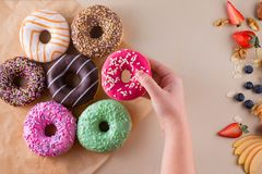 Someone`s hand holding sweet doughnut on light stone background. Someone`s hand holding sweet doughnut on a light stone background Royalty Free Stock Photos