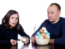 Someone's not sharing. Young man watches his wife complain at her small one scoop bowl of vanilla ice cream as hYe sits in front of his giant bowl of multi Stock Images