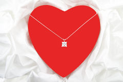 For someone special. Red heart with diamond on necklace isolated over satin Stock Image