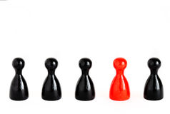 Someone special. Row of five game figurines, one red to symbolize individuality, uniqueness Royalty Free Stock Photography