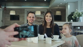 Someone taking photo on cell phone of young happy family in cafe. stock footage