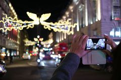 Taking a photo of the Christmas lights in London. Someone taking a photo of the Christmas lights in London Stock Photography