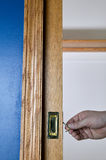 Someone unlocking a small door using their hands. Someone unlocking an open small wooden and metal pocket door using their hands by lifting a lever by a blue Stock Photos