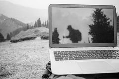 Someone uses laptop remotely at mountain. Someone uses laptop remotely with 3g or 4g network wireless at mountain, reflection of hiking tourist at monitor, black royalty free stock photo
