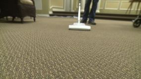 Someone vacuuming. A person vacuuming the carpet stock video