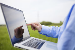 Someone working with a laptop. Conceptual shot of a person pointing at a laptop screen with a field in the background stock image