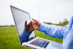 Someone working with a laptop. Conceptual shot of a person pointing at a laptop screen with a field in the background stock images