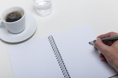 Someone writes down a note to his hotebook lying on the desktop. Coffee break on the desktop showing cup water notebook and hand writing with a pencil stock photo