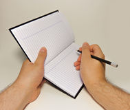 Someone writing in a notebook. A hand holding a notebook and another holding a pencil royalty free stock photo