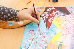 Someones hand painting Japanese landscape. Someone`s hand painting Japanese landscape indoors stock photography