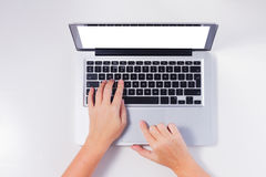 Someones hands and latop. Someones hands and laptop on white desk, top view workspace Royalty Free Stock Photography