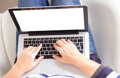 Someones hands and latop. Someones sitting om chair and using laptop, copy space on blank screen Royalty Free Stock Images