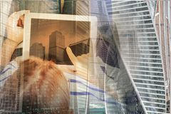 Someones hands and latop. Someones sitting om chair and using tablet, copy space on empty screen, double exposure with modern cityscape Royalty Free Stock Images
