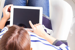 Someones hands and tablet. Someones sitting om chair and using tablet, copy space on empty screen Stock Images
