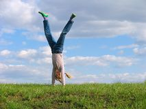 Somersault. On grass on the sky&clouds background Royalty Free Stock Image