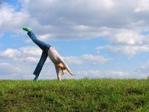 Somersault. On grass on the sky&clouds background Stock Photography