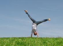 Somersault. Young pretty girl somersaults on a green grass on a background of the blue sky Royalty Free Stock Images