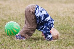 Somersault. Child with hands and head on ground moving into a somersault Stock Image