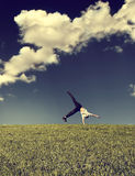 Somersault in the Field. Toned photo of Teenage Boy make Somersault in the Summer Field Royalty Free Stock Images